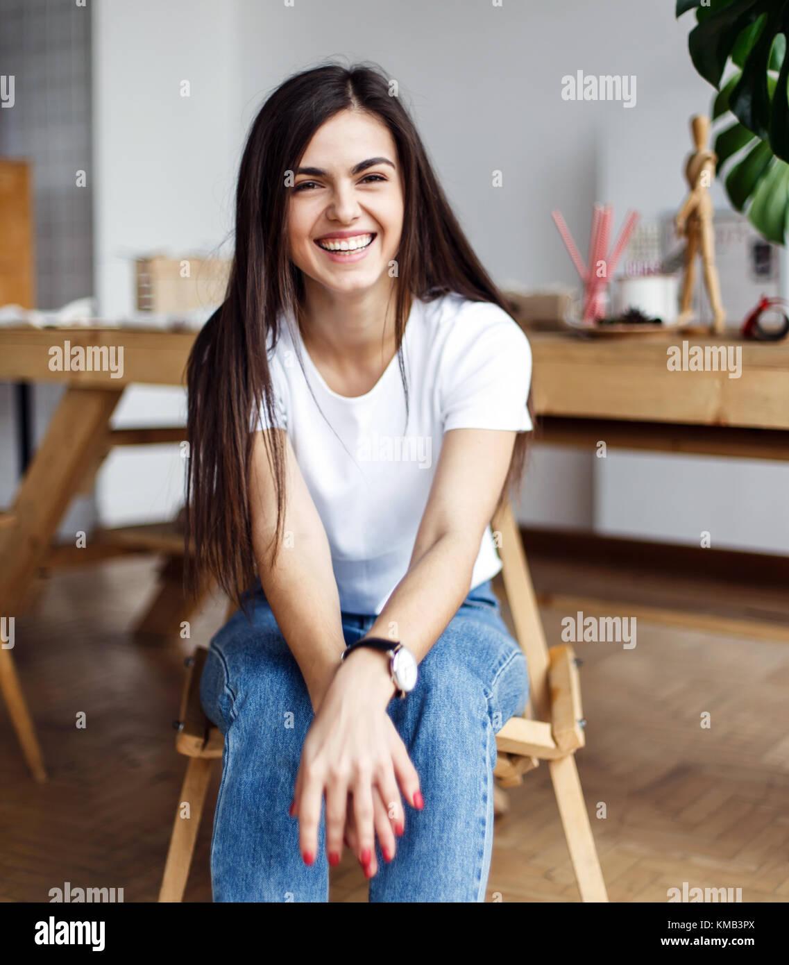 4b772fd4d Retrato de la hermosa joven viste camiseta blanca sentado en la silla de  madera en interiores
