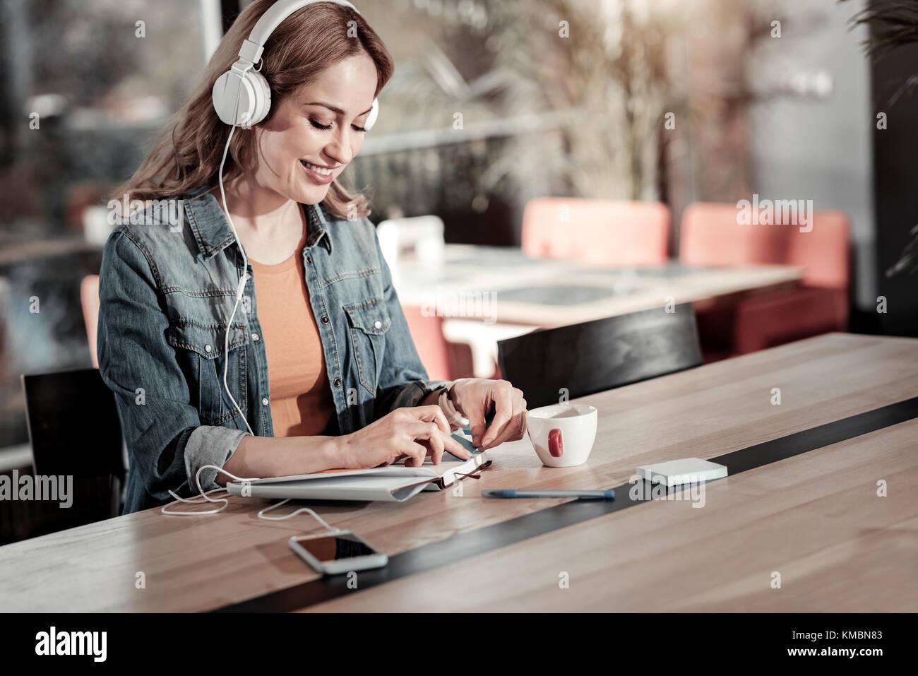 Mujer sonriente tras una mañana productiva en un café Imagen De Stock