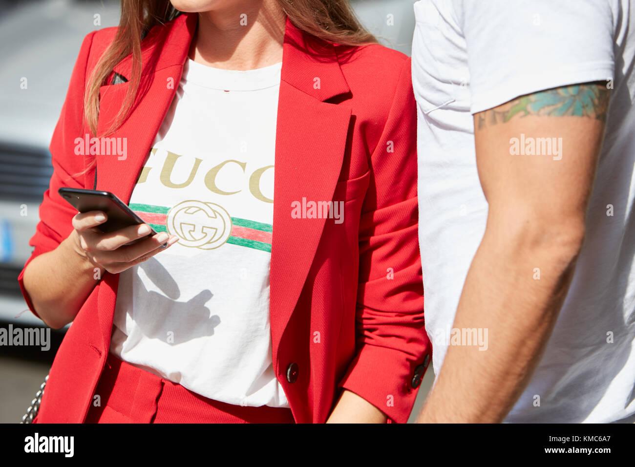 Milán - 23 de septiembre  mujer con chaqueta roja y camisa gucci mirando  smartphone antes b3b15a74a80