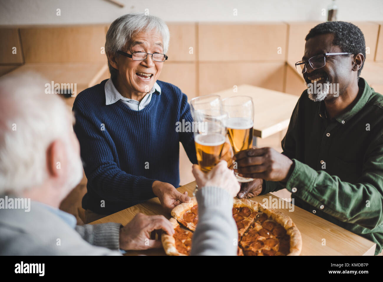 Amigos senior tintineo o vasos de cerveza Imagen De Stock