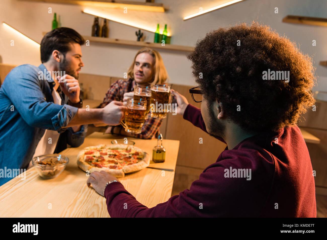 Amigos con la pizza y la cerveza en el bar Imagen De Stock