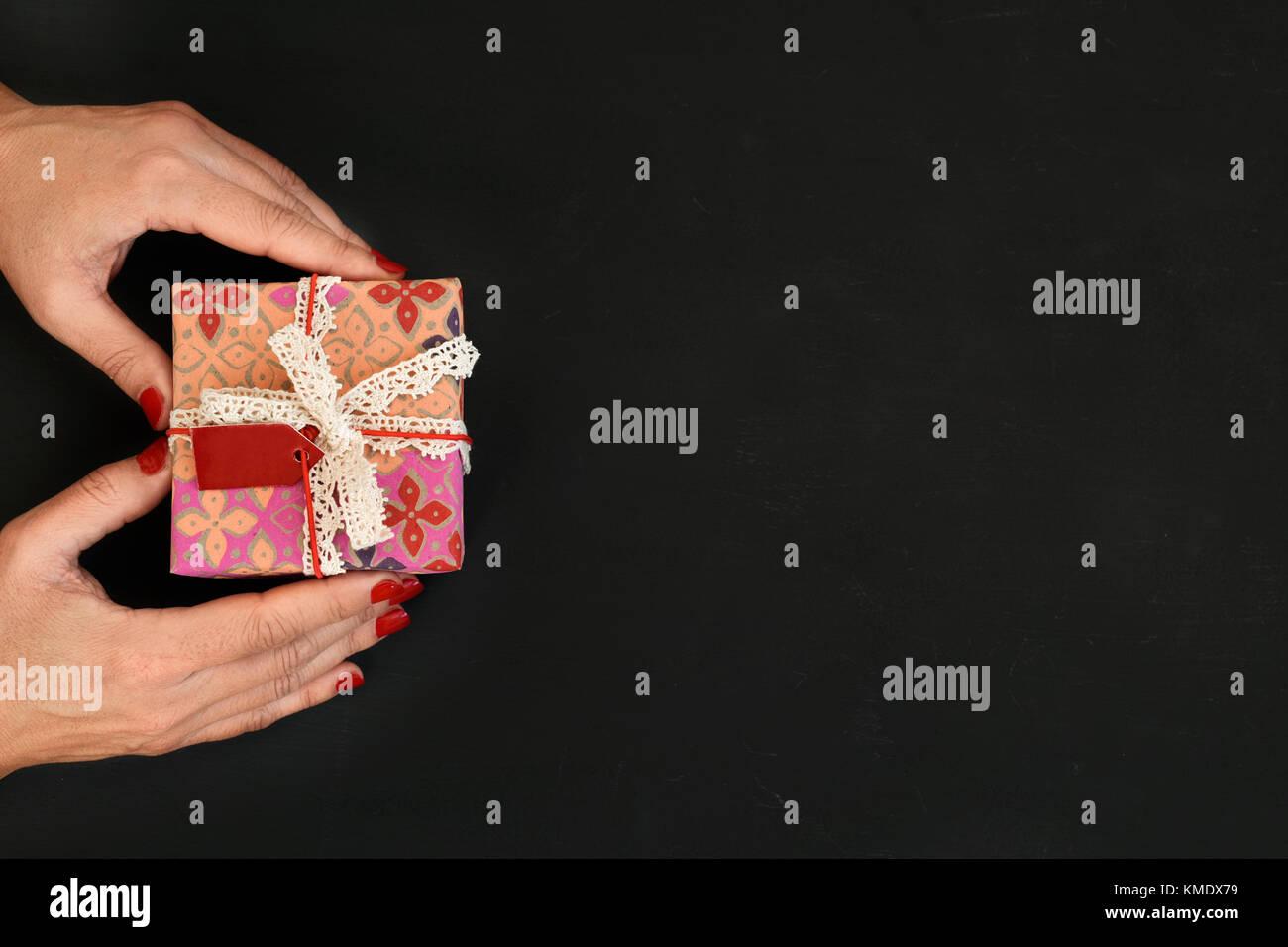 Disparo de alto ángulo de una joven mujer caucásica con un regalo en sus manos, envuelto en un lindo papel Imagen De Stock