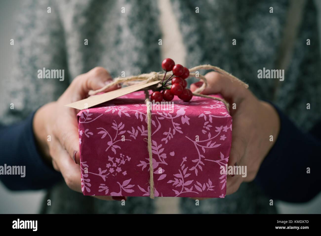 Primer plano de una joven mujer caucásica sosteniendo un regalo en sus manos, envuelto en un bonito papel rústico, Imagen De Stock
