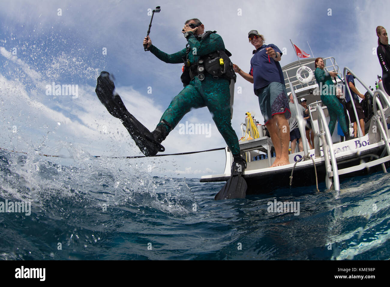 Scuba Diver entra en el agua haciendo zancada gigante. Foto de stock