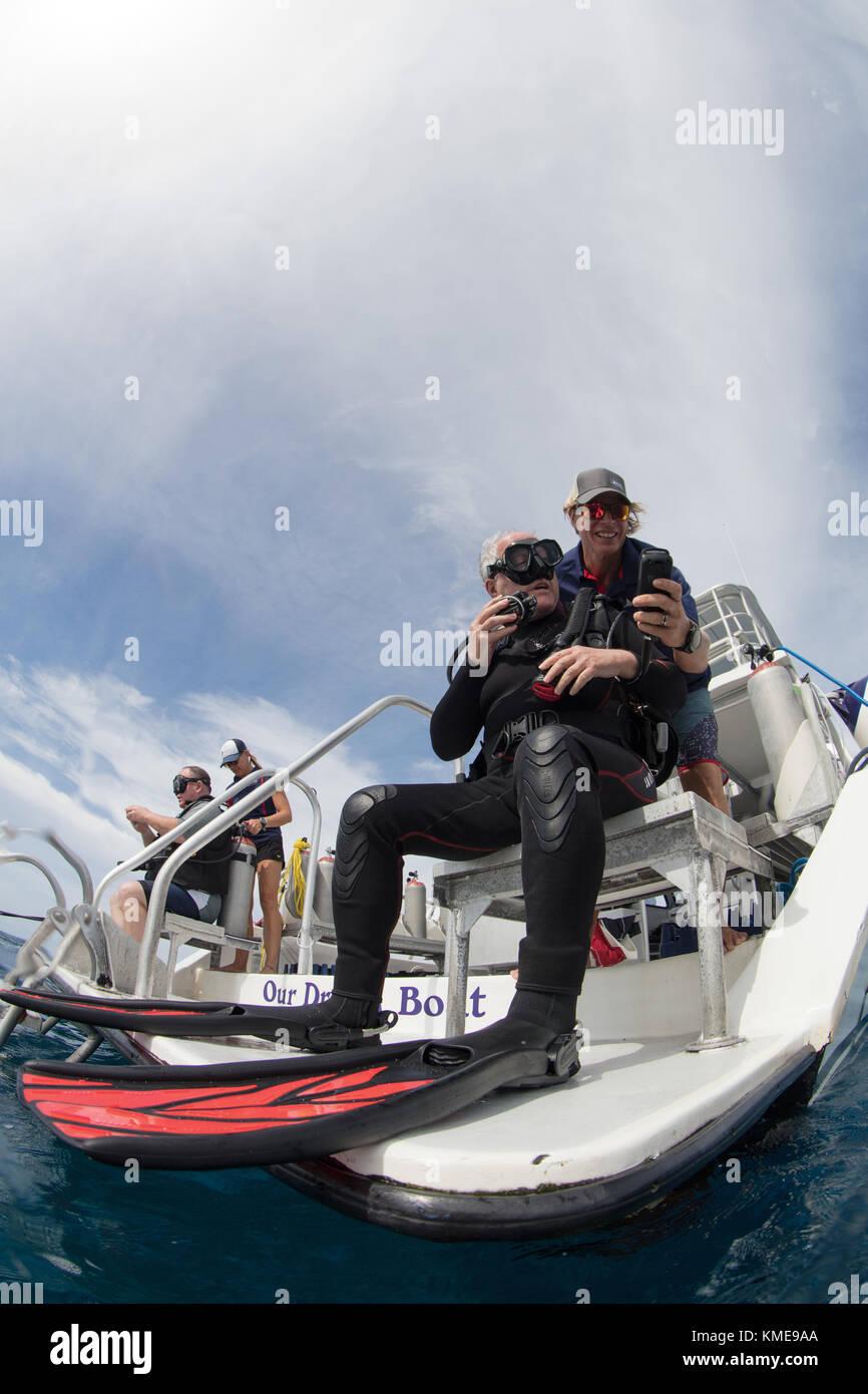 Tripulación asiste a los buzos con comprobación de seguridad antes de la entrada de agua Foto de stock
