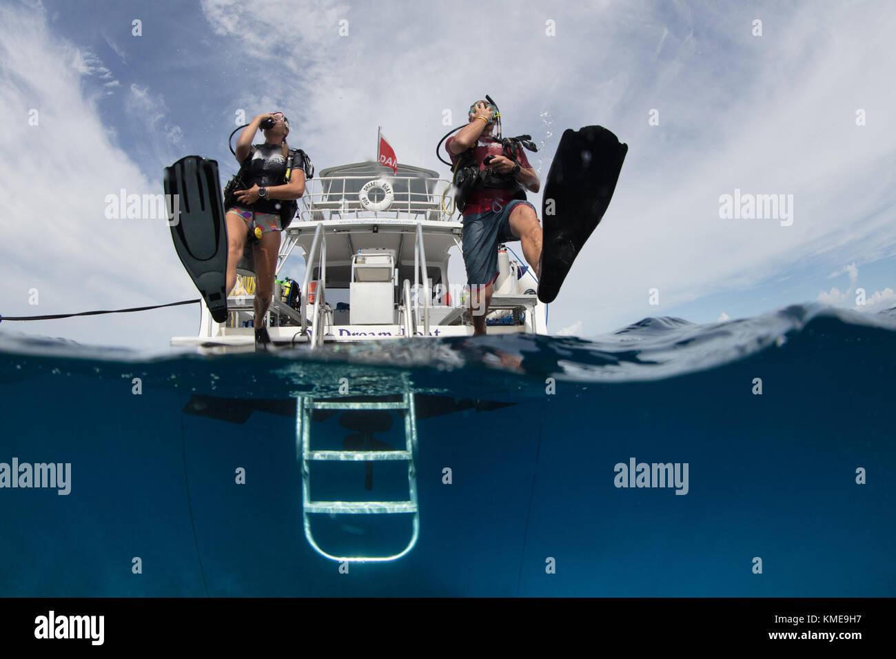 Los buzos entrar en el agua haciendo zancada gigante. Foto de stock