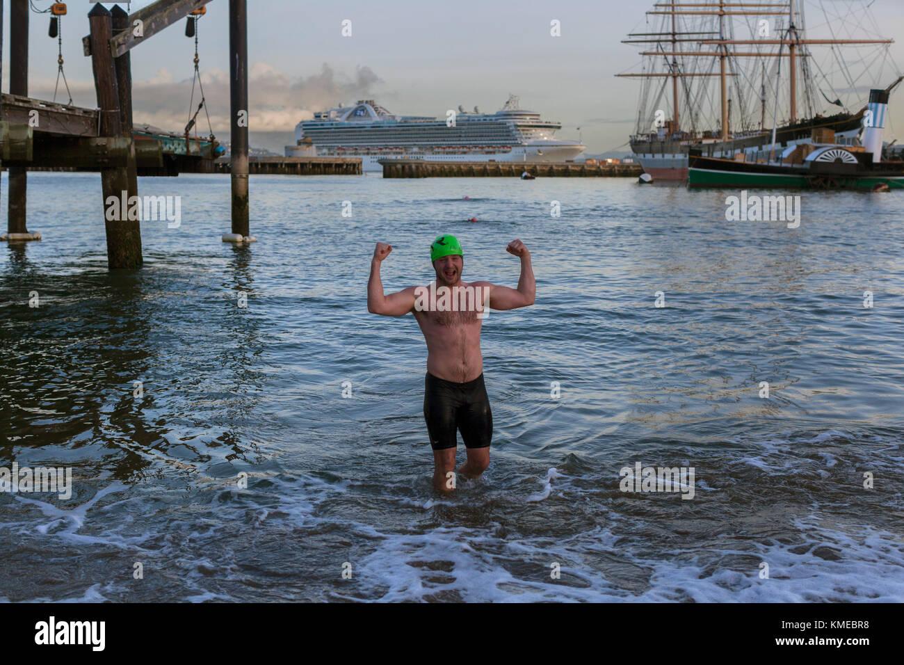 Hombre en natación troncos flexionando los músculos mientras está de pie en el agua, el Dolphin club, Imagen De Stock