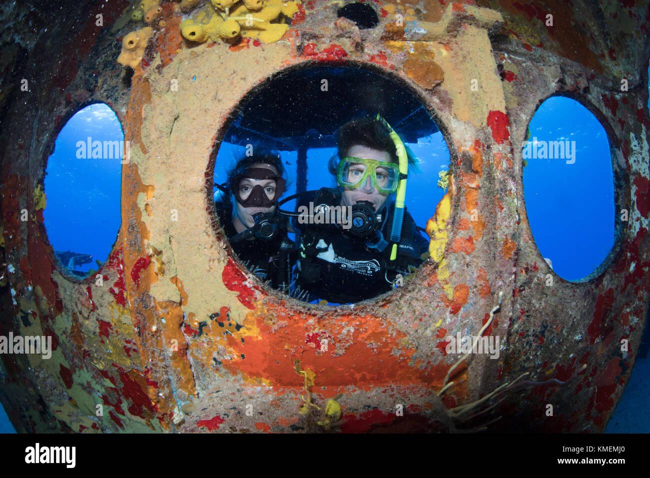 Los buceadores peer a través de ojo de buey en uss kittiwake. Foto de stock