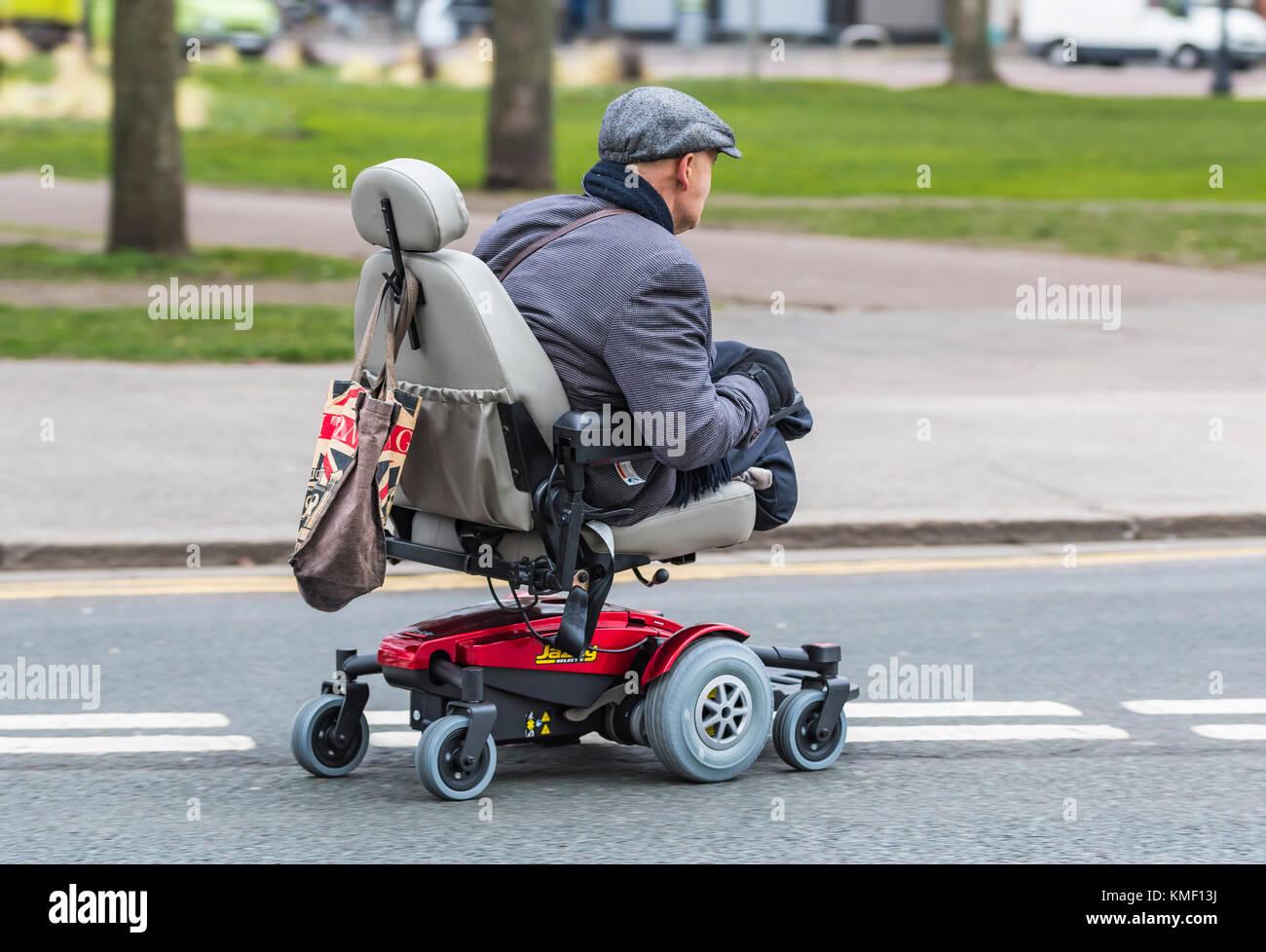 Doble amputado hombre sin piernas viajando en un scooter de movilidad en una carretera en el Reino Unido. Foto de stock