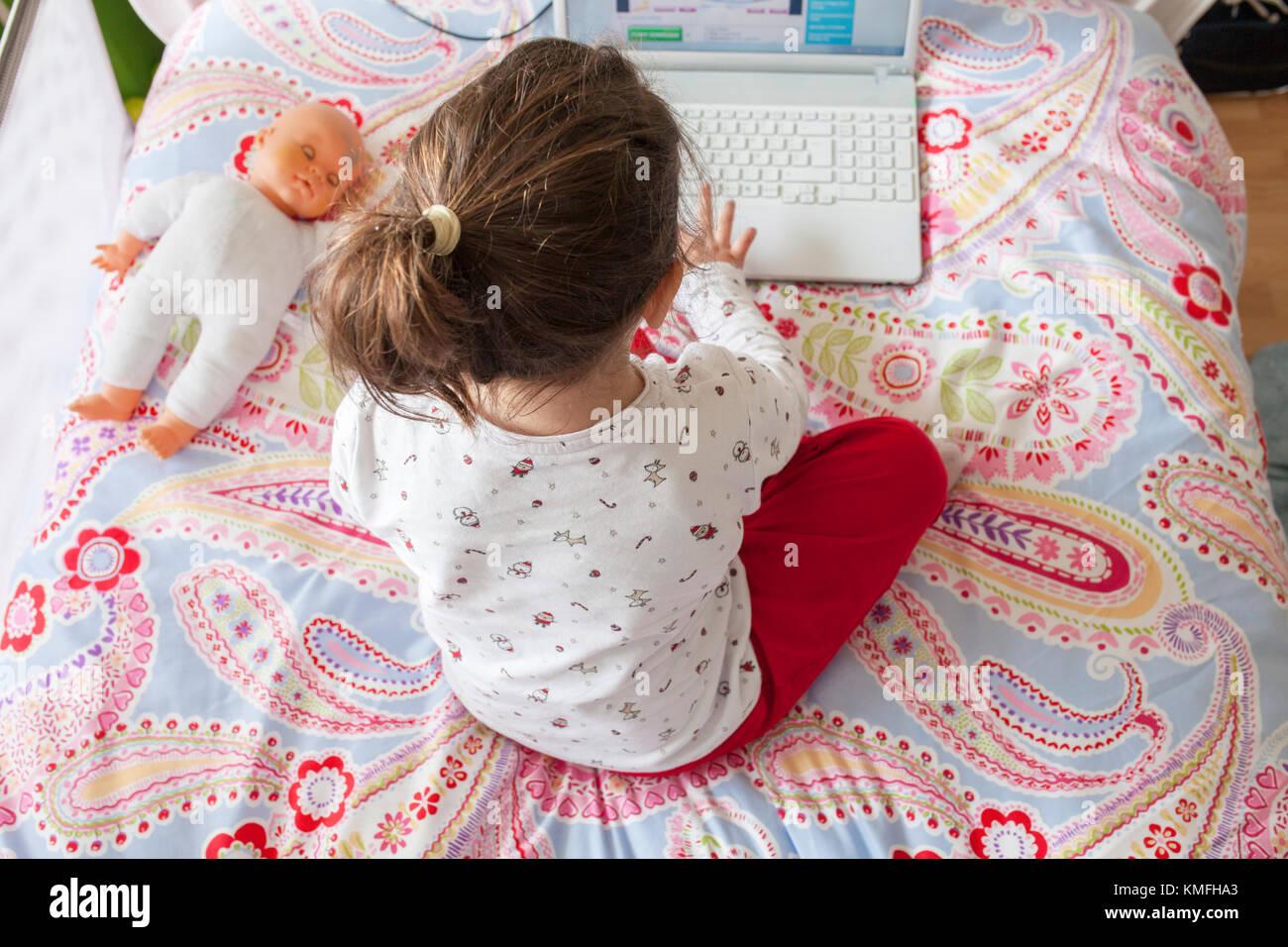 Niña sentada en la cama y jugar en línea en su dormitorio un alto ángulo de visualización. Imagen De Stock