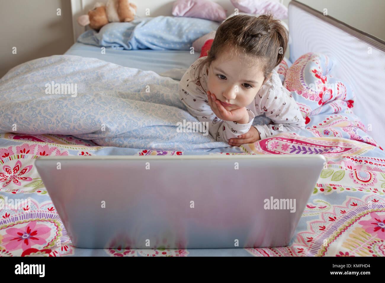 Niña acostado en la cama y jugando con un portátil en su dormitorio. Ella espera atenta Imagen De Stock