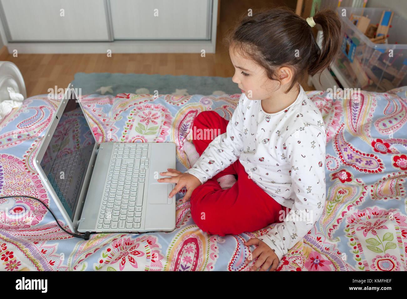 Niña sentada en la cama y jugar en línea en su dormitorio Imagen De Stock
