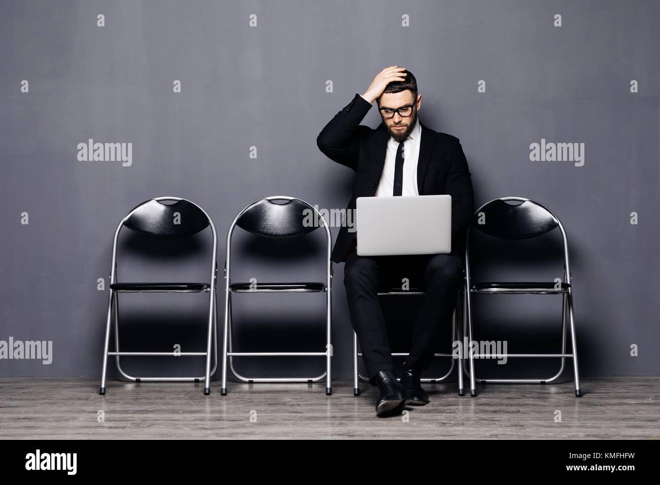 Joven en traje sentado en una silla con el portátil y a la espera de una entrevista de trabajo Imagen De Stock