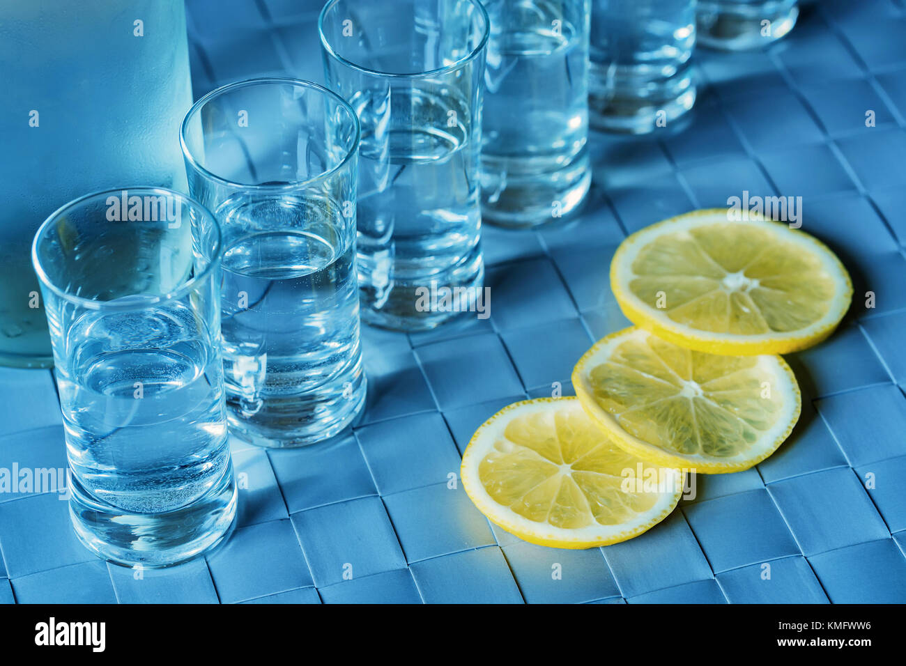 Vodka shot glass y limón sobre la superficie azul Imagen De Stock