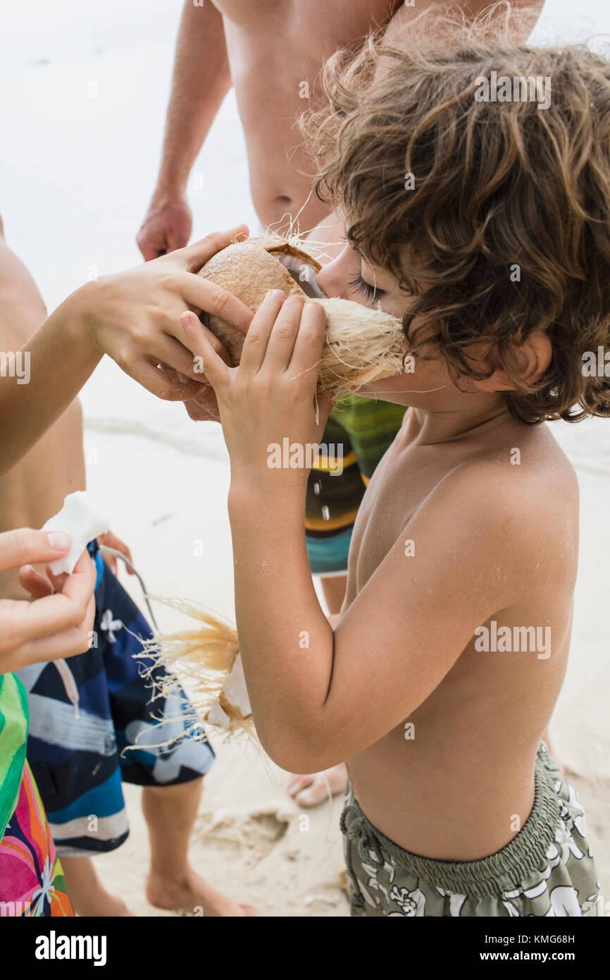 Niños compartiendo un coco en la playa. Imagen De Stock
