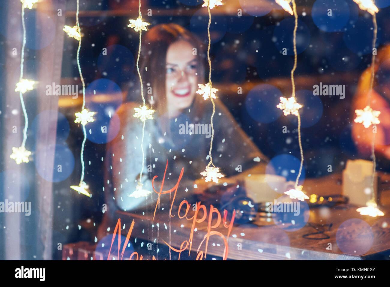 Hermosa joven mujer sentada en la cafetería, bebiendo café. Las nevadas efecto mágico. Feliz Navidad, Imagen De Stock