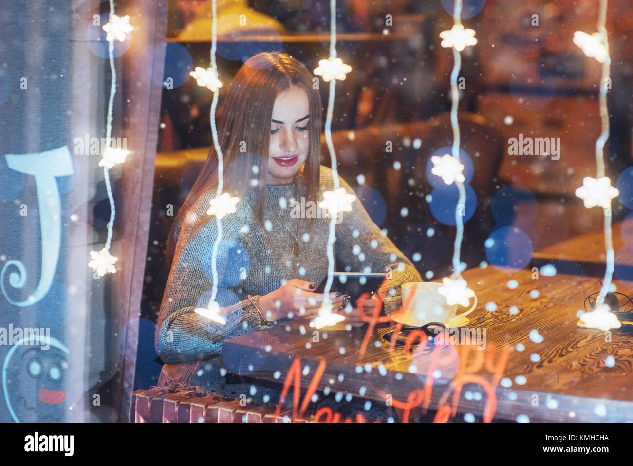 Hermosa joven mujer sentada en la cafetería, bebiendo café. Las nevadas efecto mágico. Feliz Navidad, Año Nuevo, Foto de stock