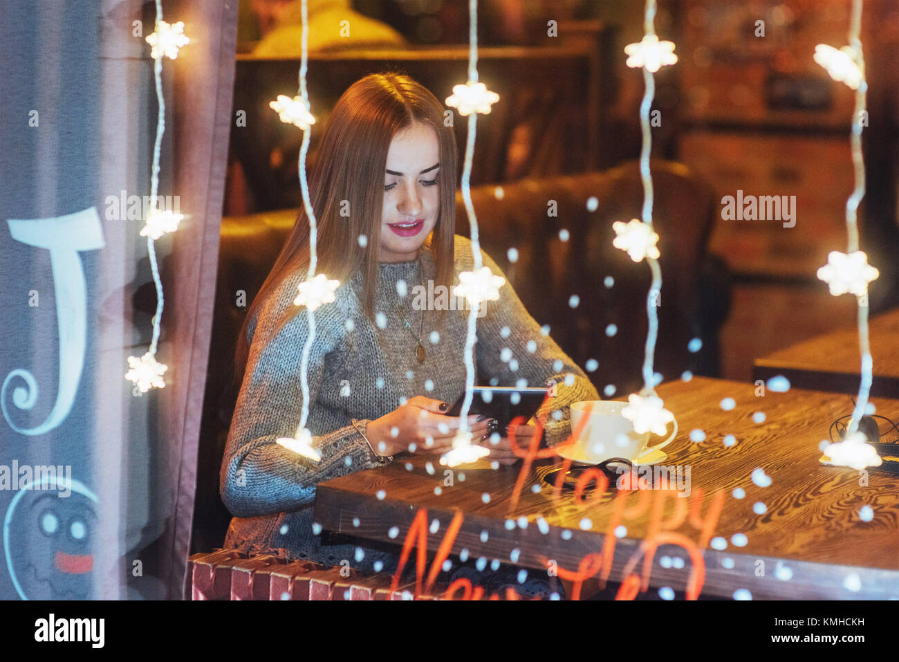 Hermosa joven mujer sentada en la cafetería, bebiendo café. Las nevadas efecto mágico. Navidad, Año Imagen De Stock