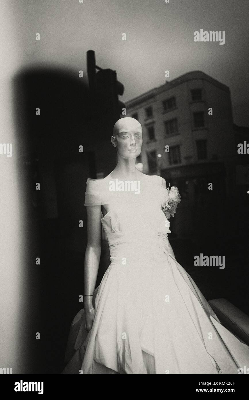 fc6849e418c Escaparate con maniqui en traje de novia. La reflexión de la construcción  en vidrio. Londres, Inglaterra