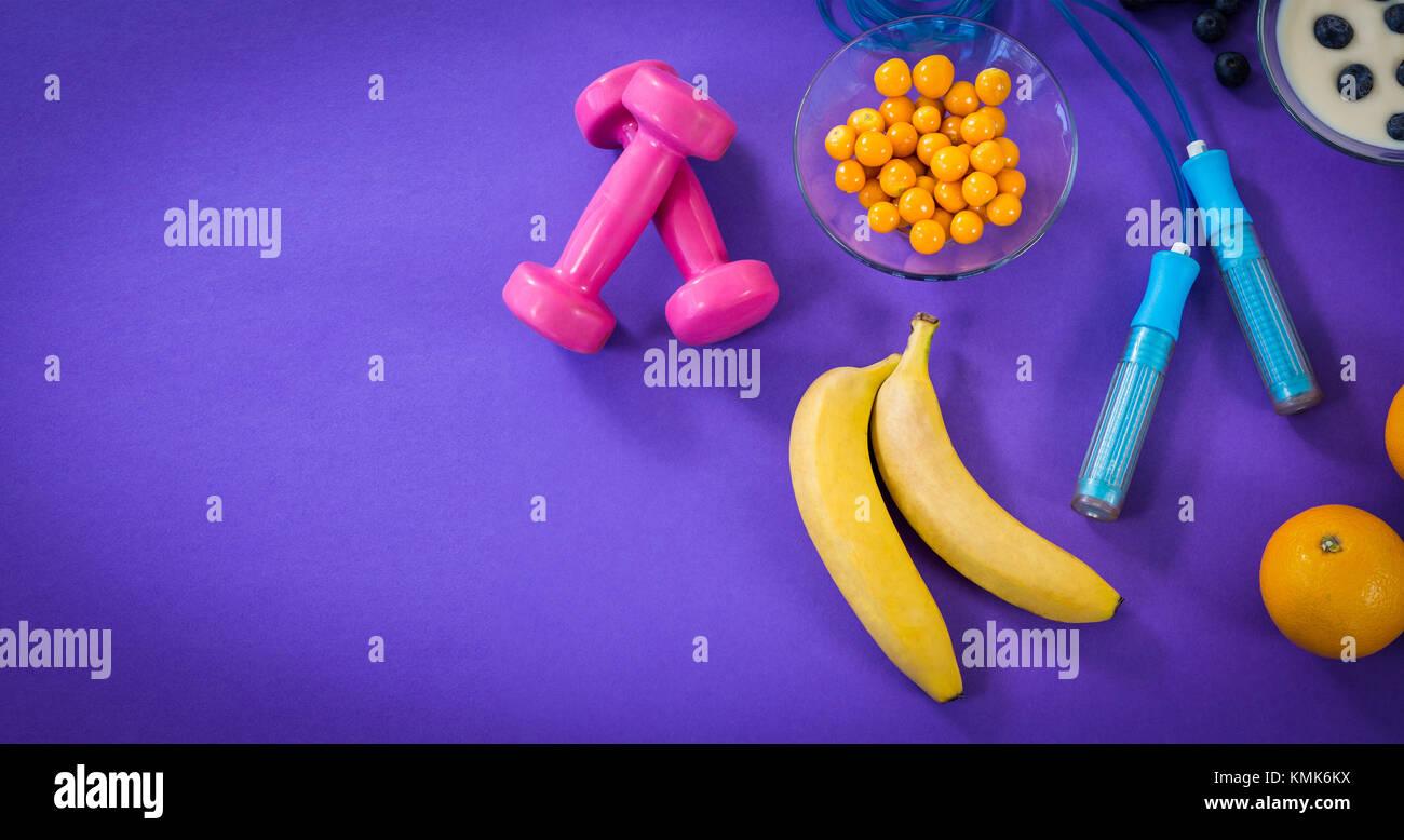 Un alto ángulo de visualización de alimentos con equipo de ejercicio contra el fondo violeta Imagen De Stock