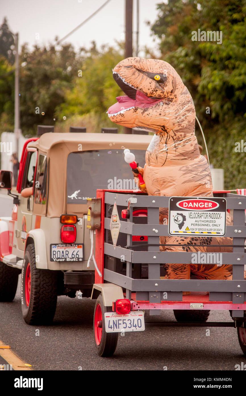 Un monstruo jurásico murgas obtiene un paseo en un remolque detrás de un jeep en una ciudad aniversario Imagen De Stock