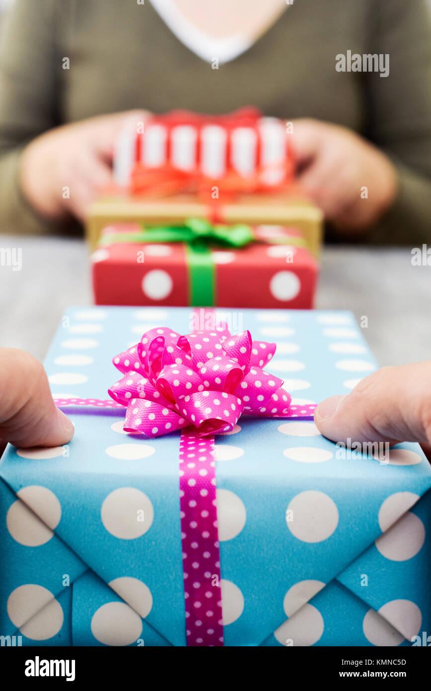 Primer plano de una joven mujer caucásica y un joven hombre caucásico intercambiando regalos sobre una Imagen De Stock