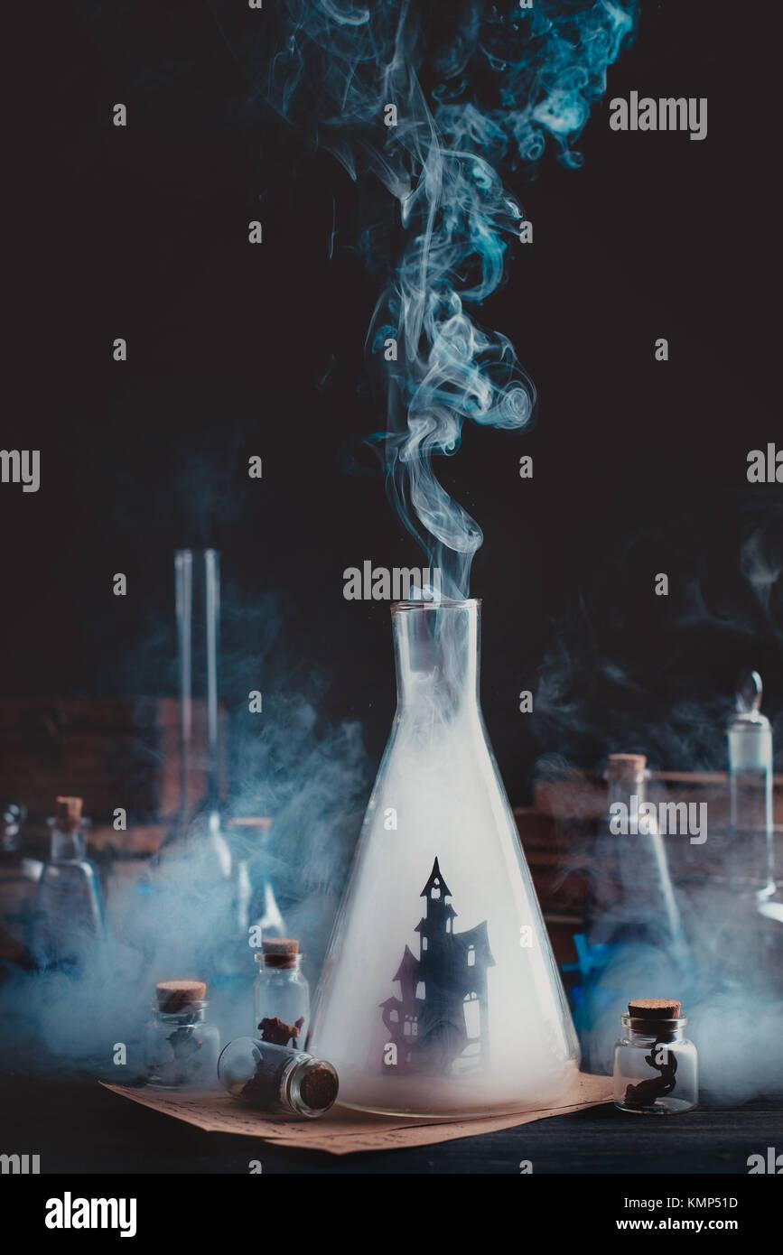 Botella de laboratorio con la silueta del castillo embrujado. Asistente de trabajo con humo y equipo mágico. Imagen De Stock