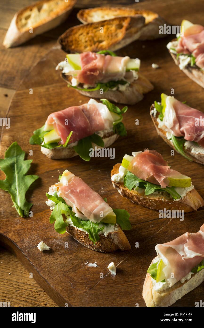 Prosciutto caseras queso pera crostini con rúcula Imagen De Stock