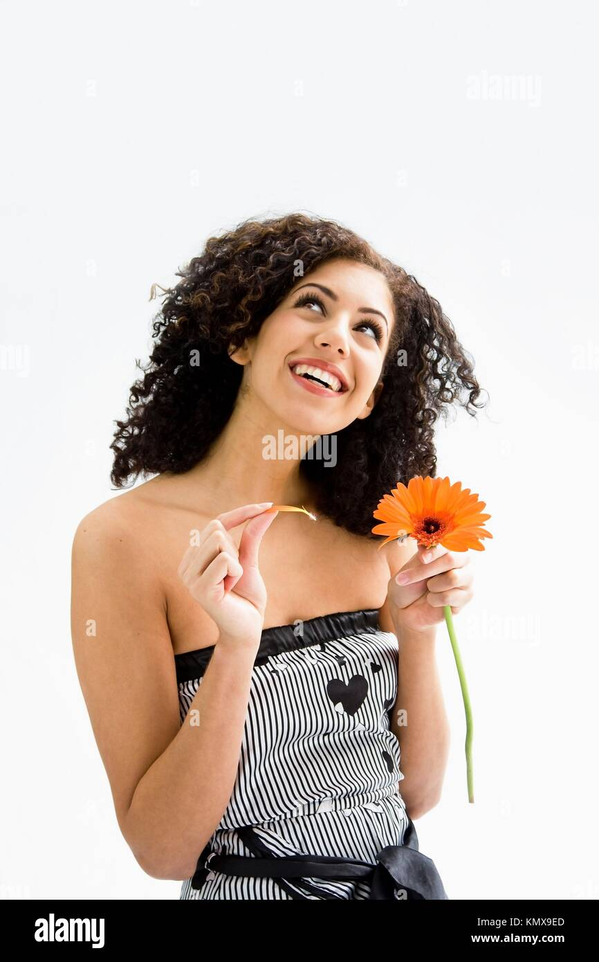 Feliz sonriente joven hermosa con marrón rizado cabello salvaje y flor de  naranja en la mano ef49e55e232
