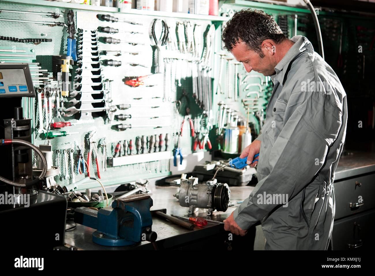 Cerca de una sonriente mecánico dentro de su taller de reparación de automóviles Imagen De Stock