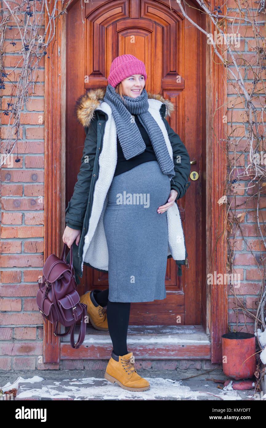 800f9e61d2c Una mujer embarazada en un sombrero de color rosa tejida, un traje gris,  una chaqueta abrigada y con una mochila sonriendo y salió a caminar en un  invierno ...