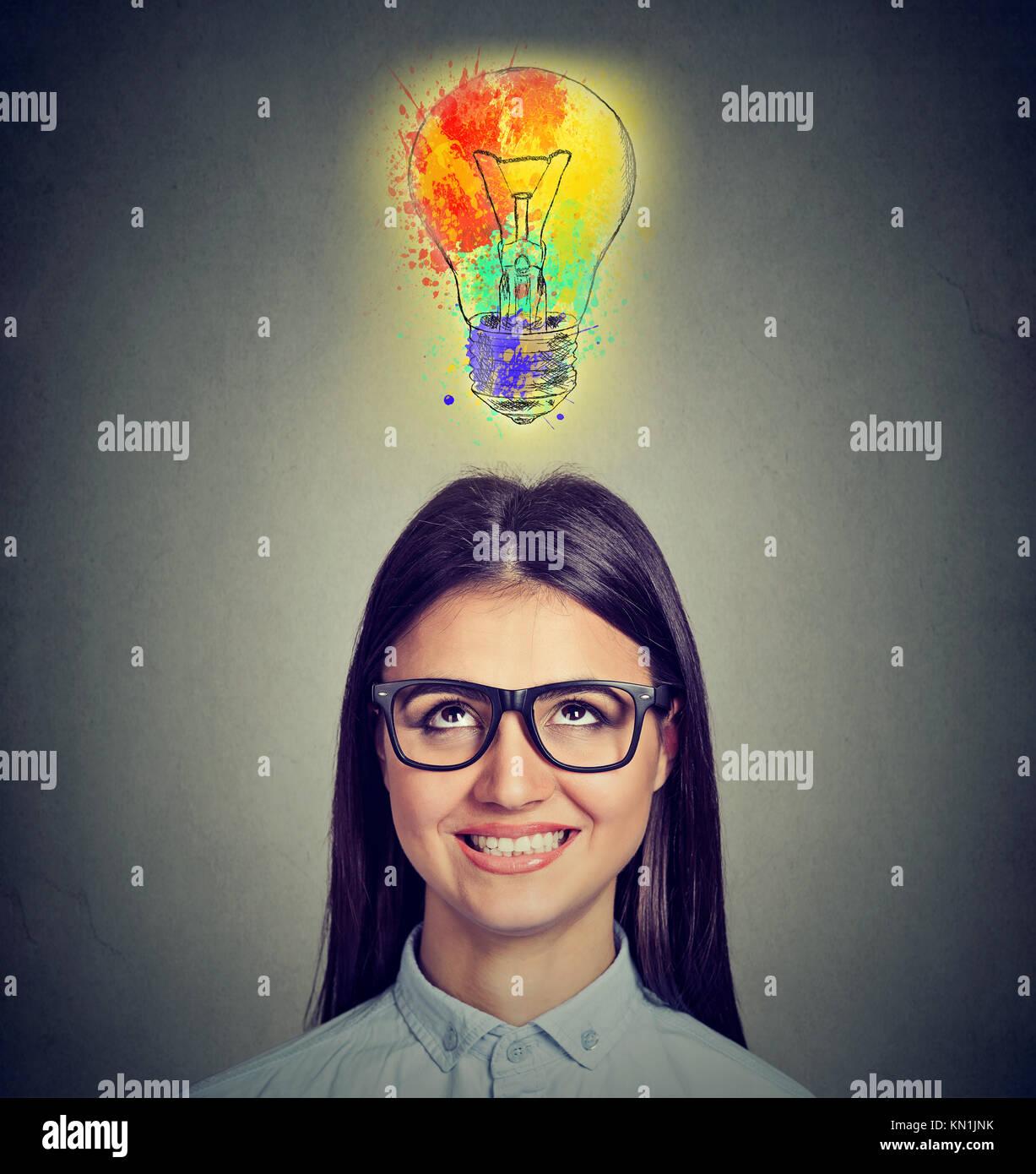 Retrato de una mujer con gafas y creativa idea mirando la bombilla de luz multicolor sobre fondo gris. Concepto Imagen De Stock