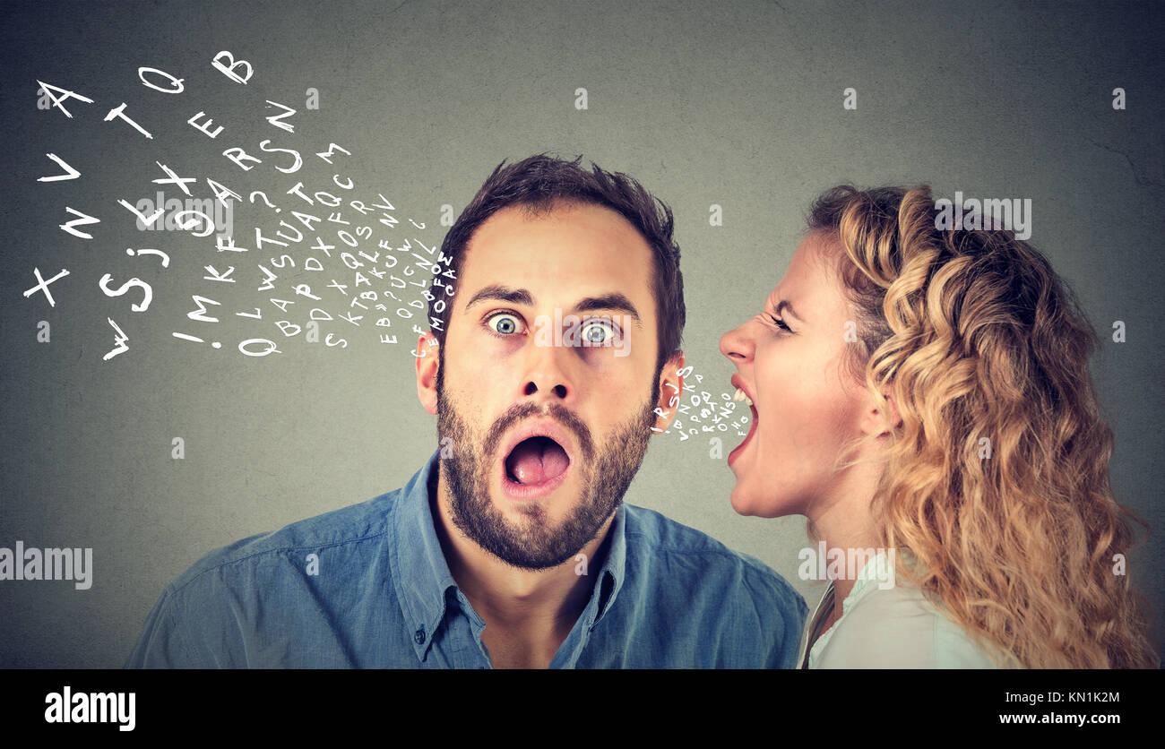 Mujer furiosa gritando algo en el oído de un chico asustado, sorprendido, aislado en la pared gris de fondo. Imagen De Stock