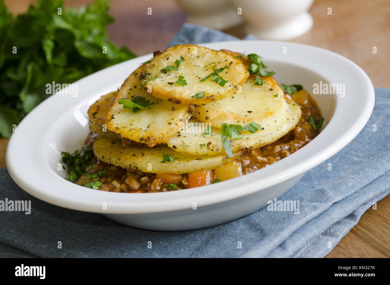 Cordero picada, en trozos grandes las zanahorias y los guisantes en una rica salsa, rematada con patatas asadas. Imagen De Stock