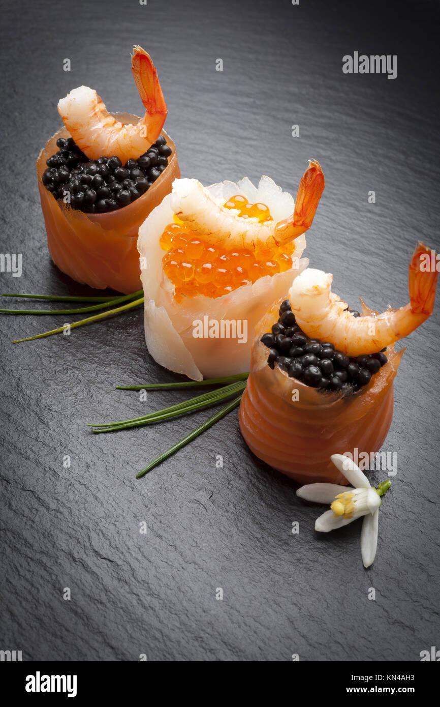 Canapés de trucha con gambas y salmón ahumado y caviar. Imagen De Stock