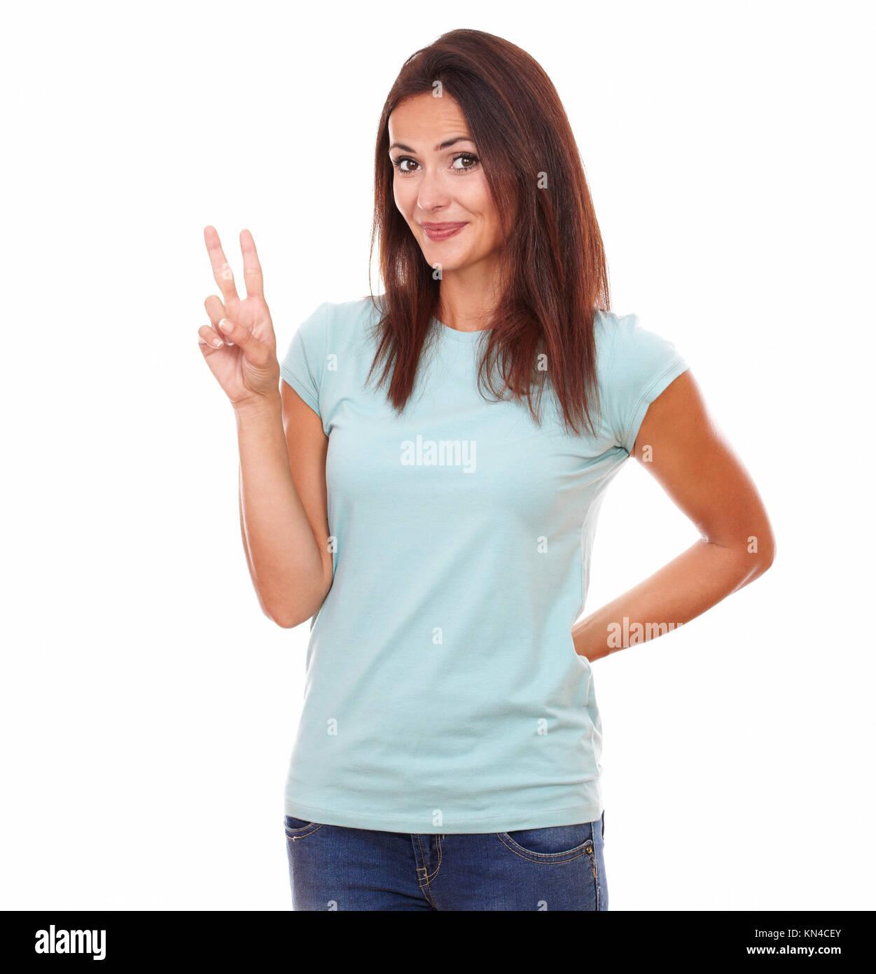 Retrato de 30-35 años amable mujer encantadora en la camiseta azul con signo ganadora sonriendo mientras está Imagen De Stock