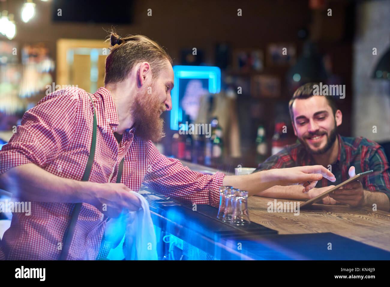 Bartender ayudando huéspedes elegir bebidas Imagen De Stock