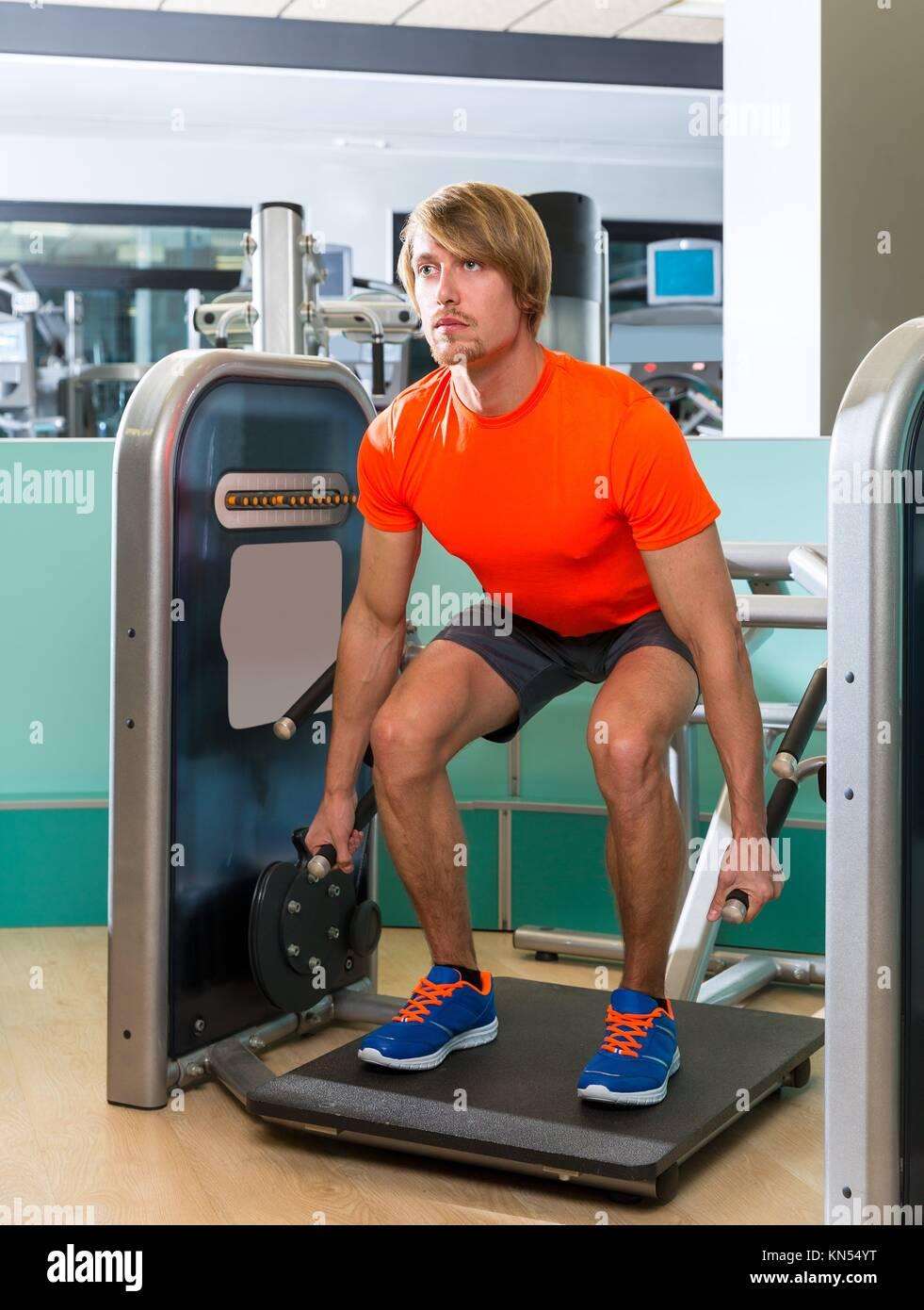 Gimnasio máquina sentadilla ejercicio workout rubio en interiores. Imagen De Stock