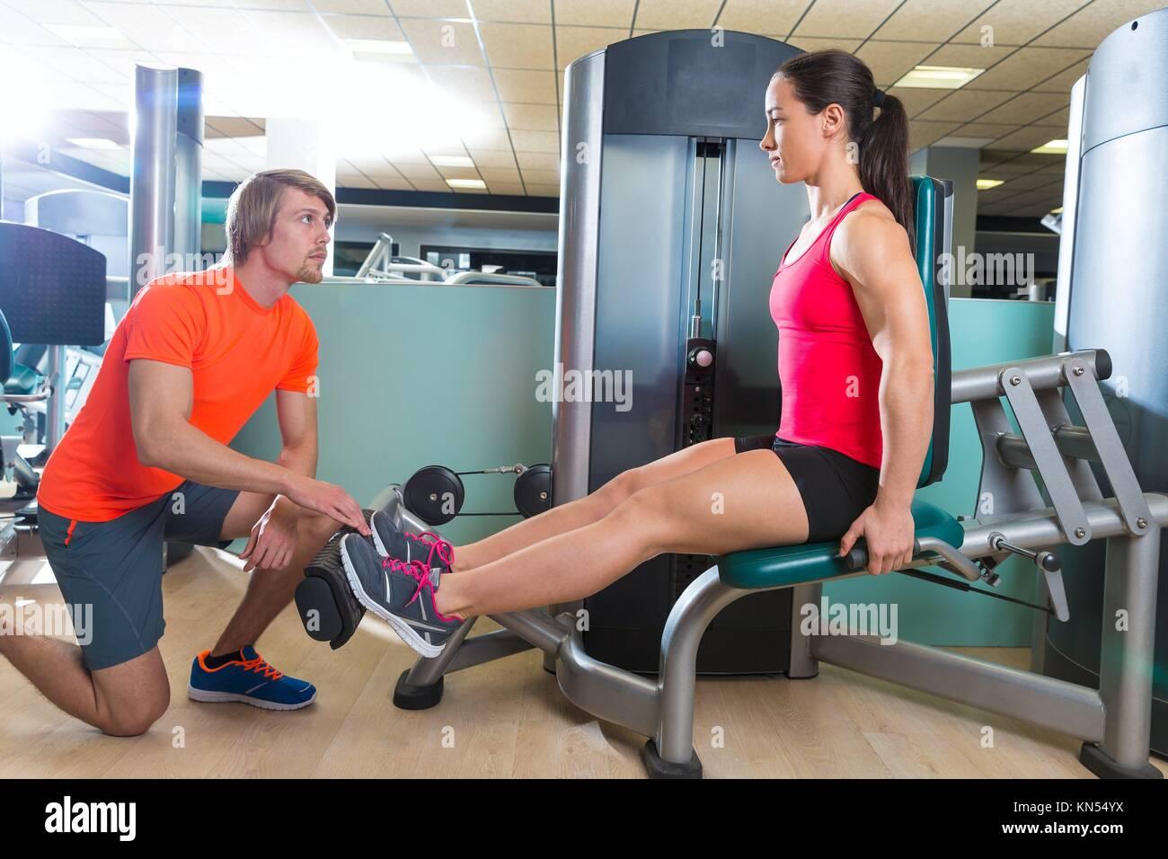Mujer en la extensión de la pantorrilla máquina de ejercicios de entrenamiento de gimnasio y entrenador Imagen De Stock