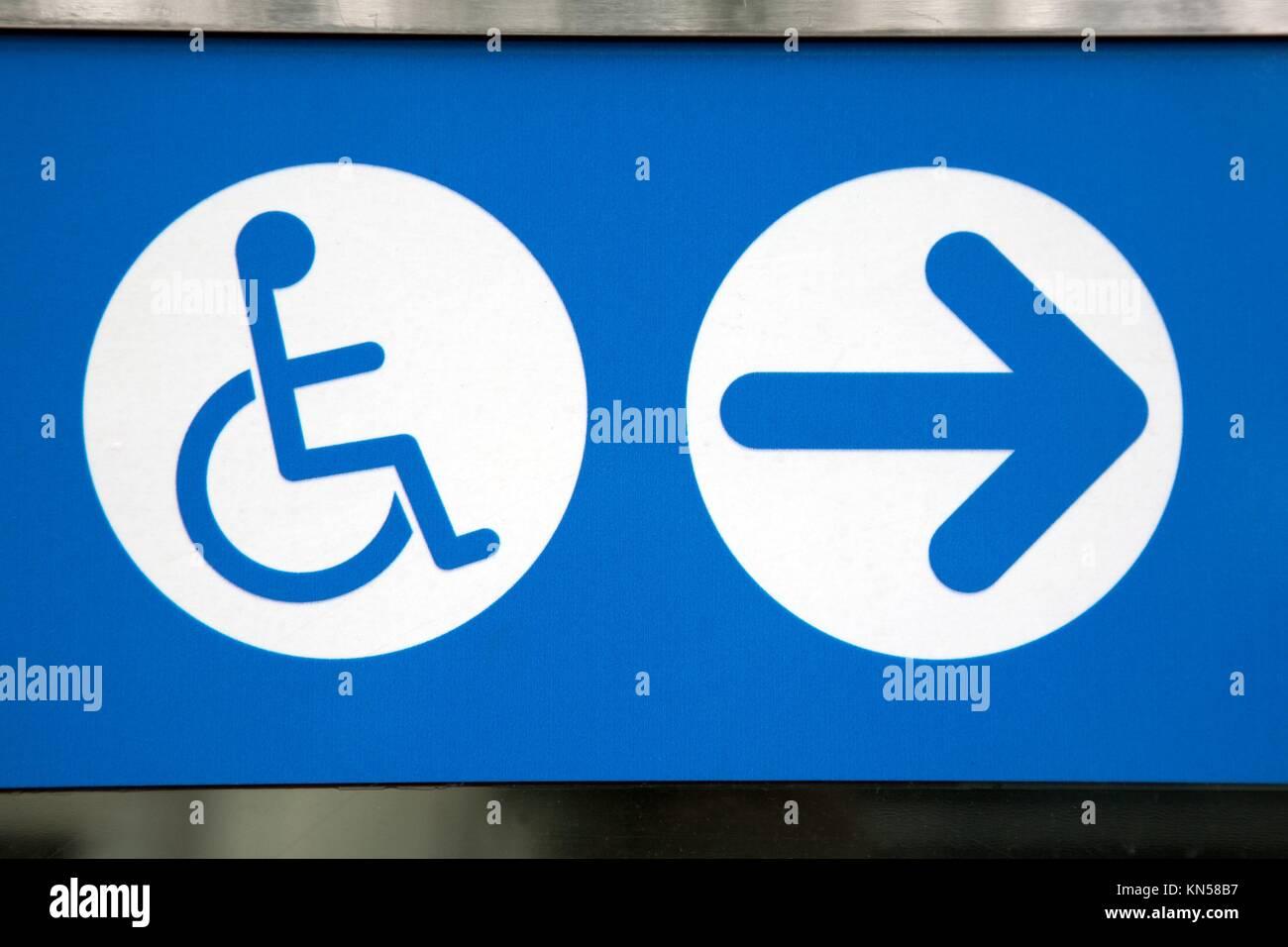 Señal de Discapacitados de color azul y blanco con la dirección de la flecha. Foto de stock