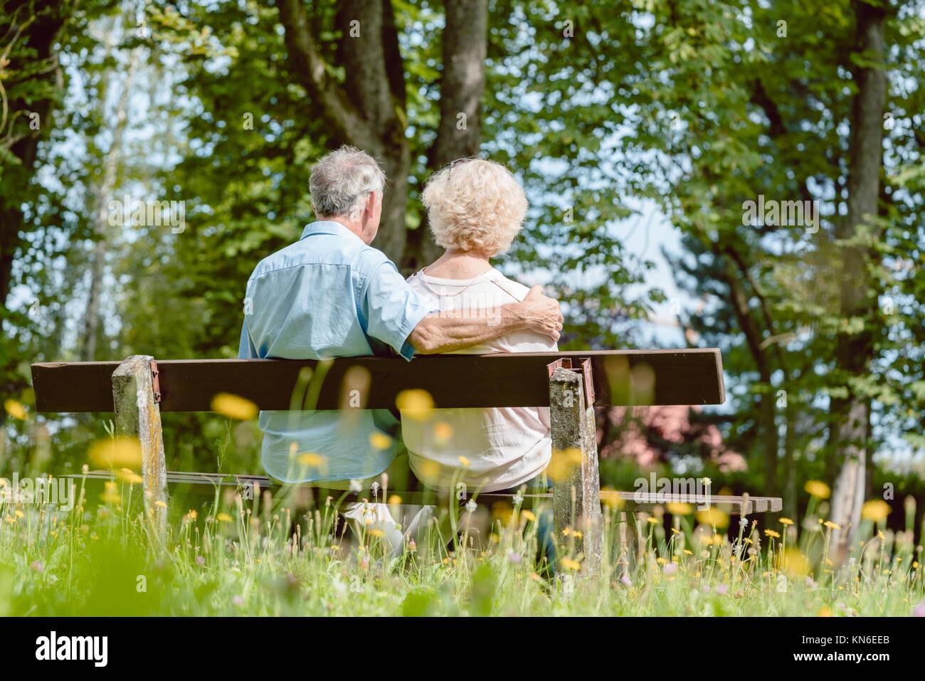 Romántica pareja de ancianos sentados juntos en un banco en una tranqui Imagen De Stock
