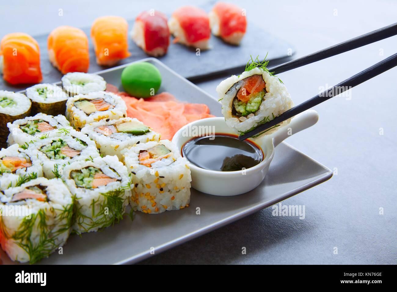 Maki Sushi y Niguiri con salsa de soja y wasabi con California Roll. Foto de stock
