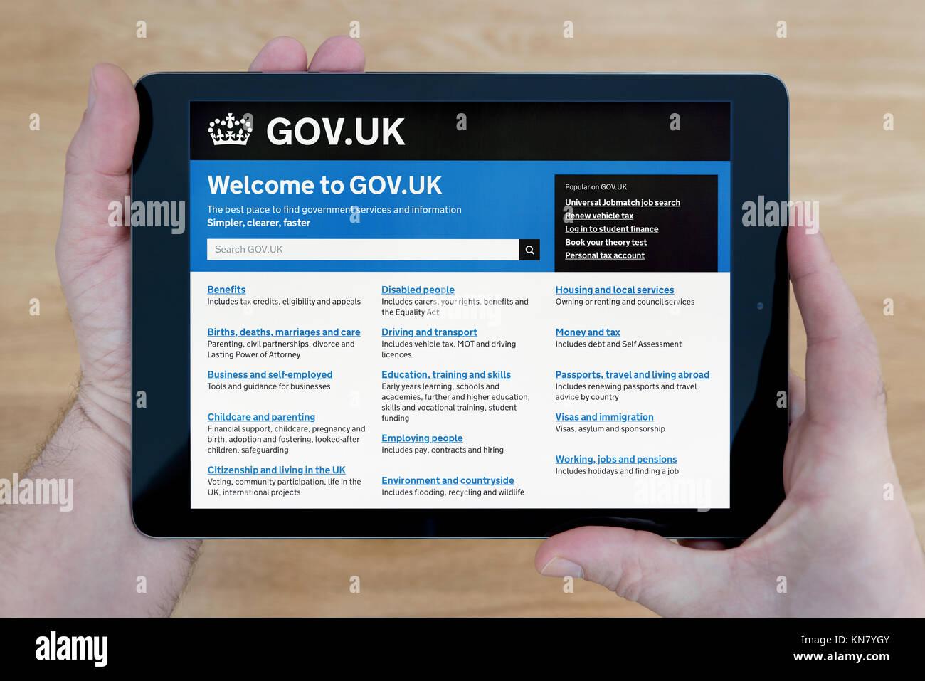 Un hombre mira el gov.uk sitio web sobre su dispositivo iPad, disparó contra una mesa de madera fondo superior Imagen De Stock