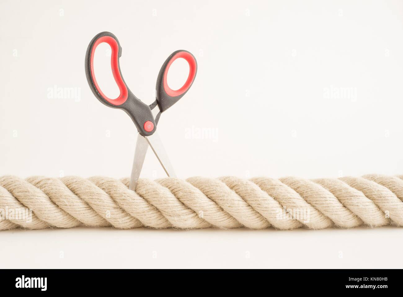 La soga fuerte y unas tijeras pequeñas. Concepto de fuerza, desafíos y dificultades. Foto de stock