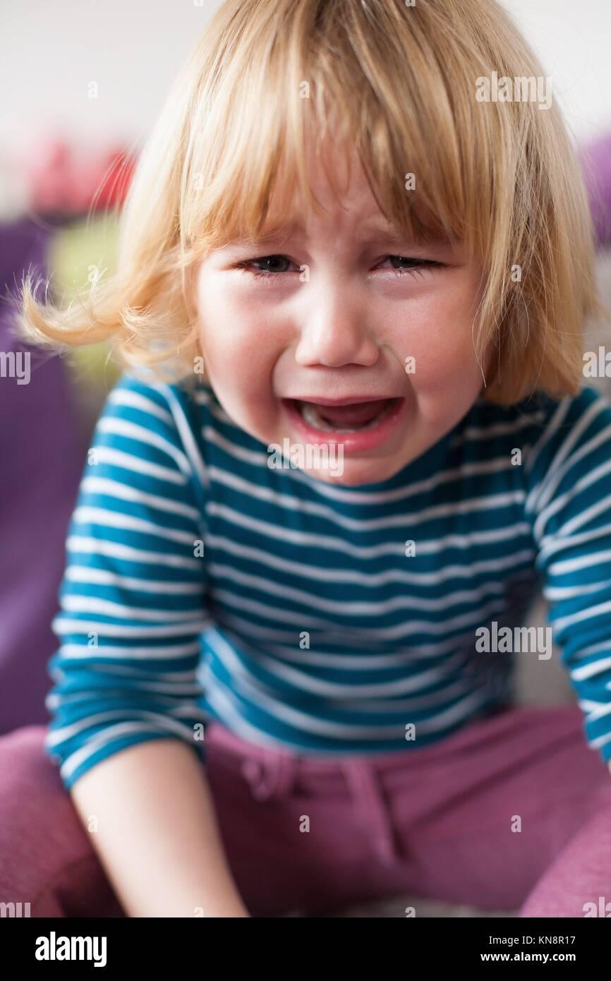 Retrato de niño de dos años rubia con rayas blancas y azules sweater sentado y llorando mirando. Imagen De Stock