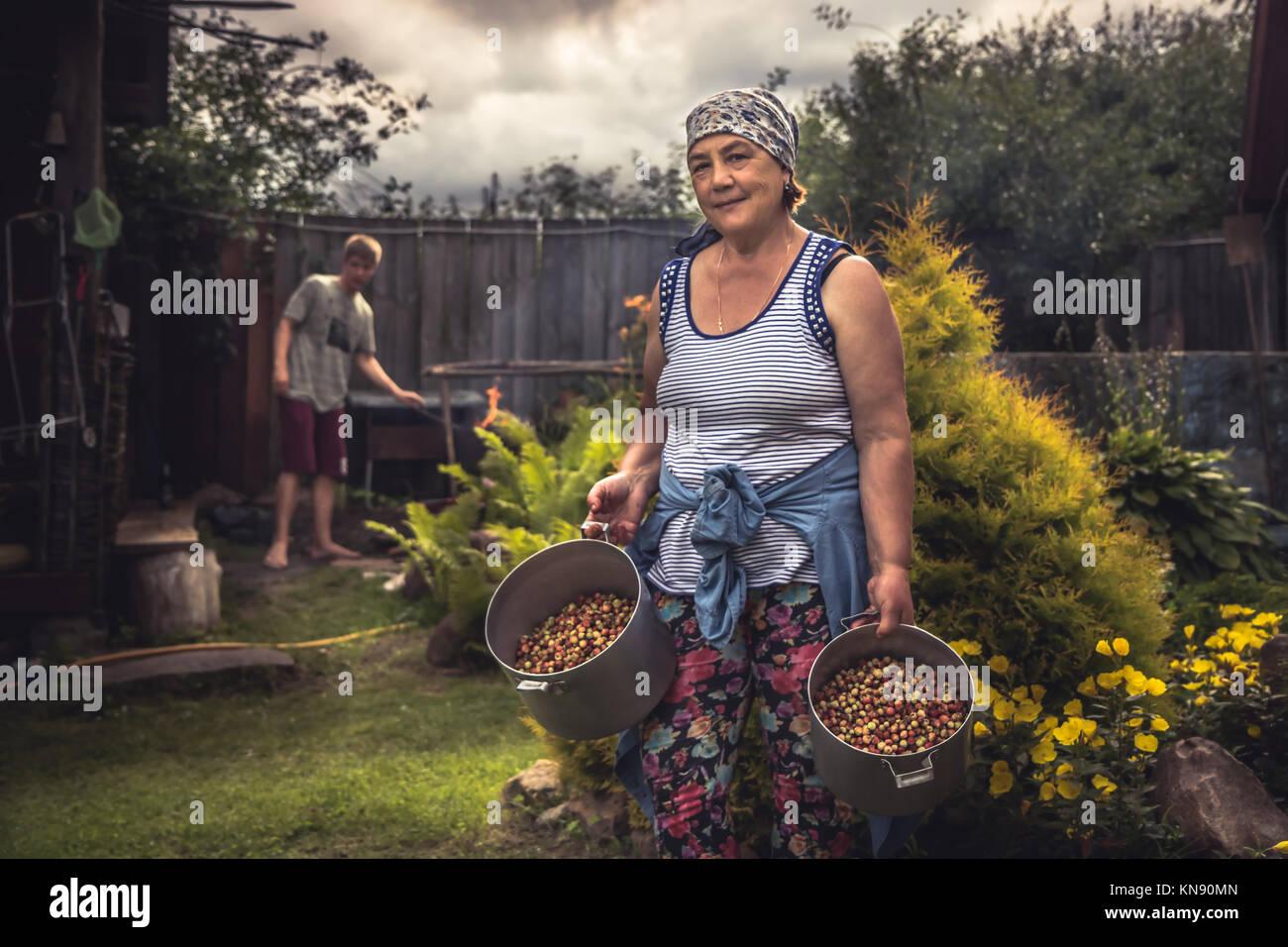 Alegre altos de la mujer campesina en el jardín con la cosecha de fresas maduras durante el verano temporada de Foto de stock
