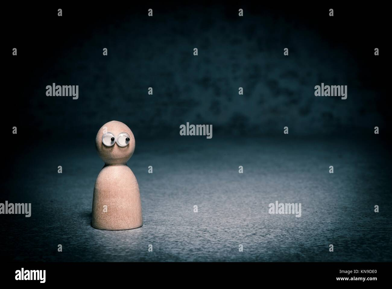 Símbolo de la soledad y la depresión. Pequeña figura sola en la oscuridad mirando nerviosa lateralmente. Imagen De Stock