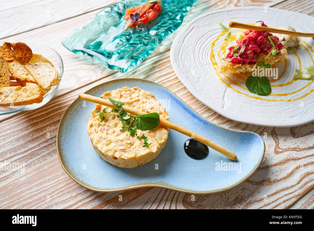Alimentos entrantes ensalada de papas steak tartare y anchoas con tomate Tapas. Imagen De Stock