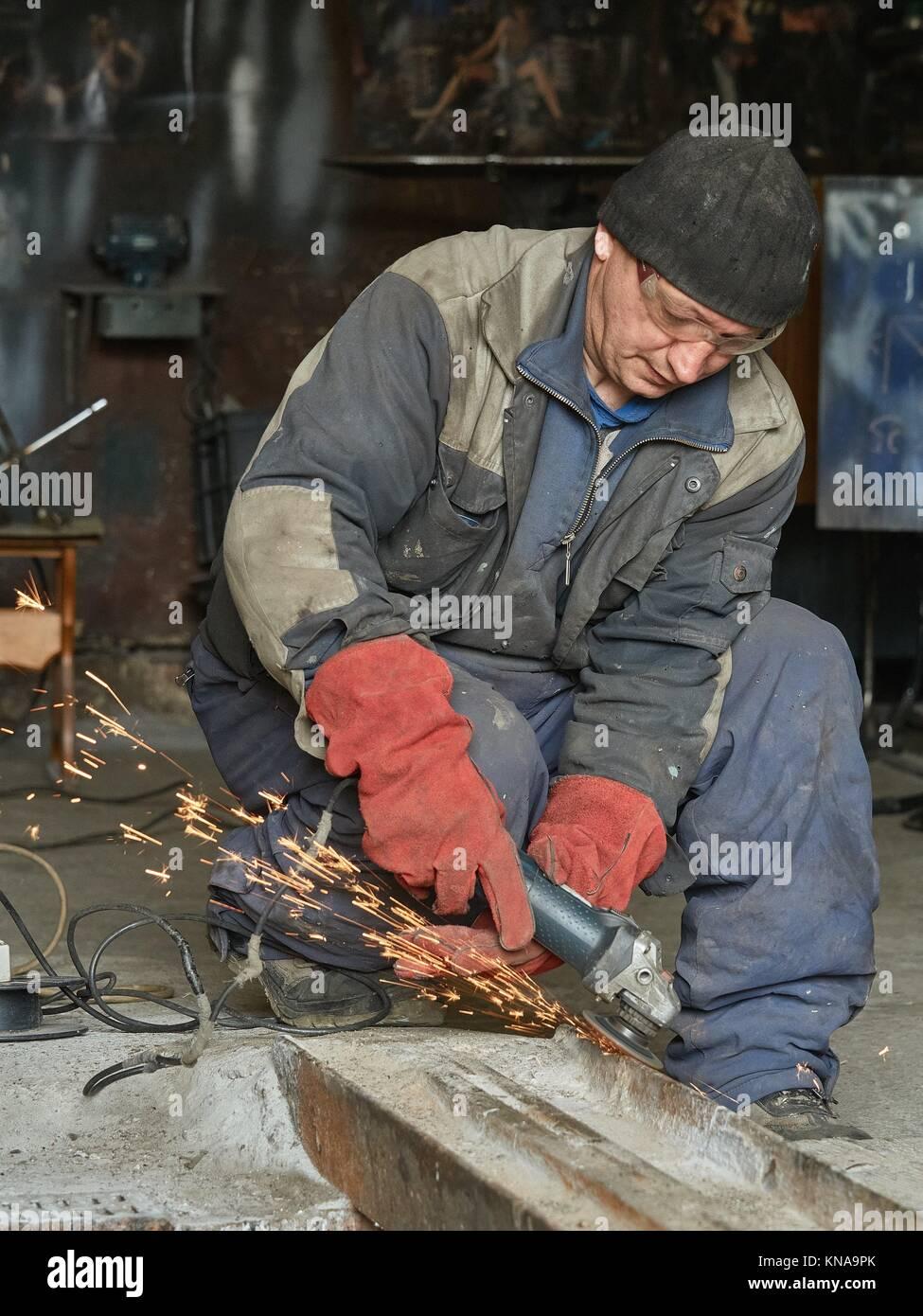 Muele trabajador ferroviario de metal para su posterior soldadura. La foto muestra las chispas de la muela. Imagen De Stock