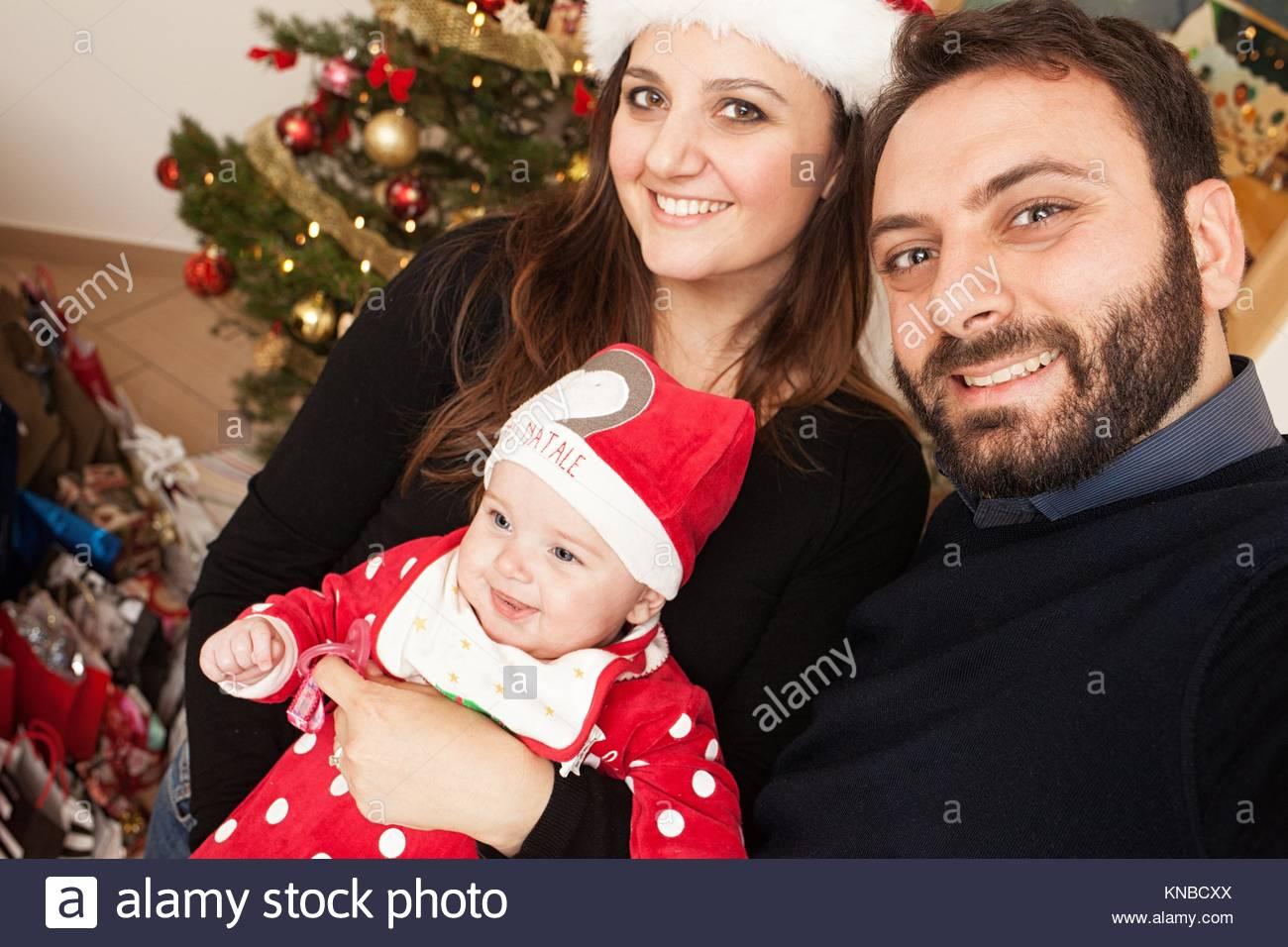 Selfie de bebé niña, con traje de Navidad y su mamá y papá. Imagen De Stock